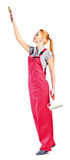 Young woman in red overalls with painting tools Stock Photography