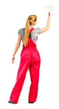 Young woman in red overalls with painting tools Royalty Free Stock Photography