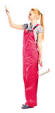Young woman in red overalls with painting tools Stock Image