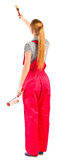 Young woman in red overalls with painting tools Stock Images