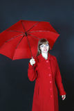 Young woman in red overcoat stands with umbrella. And smiles in black studio Stock Photography