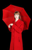 Young woman in red overcoat with umbrella. On black background Royalty Free Stock Photo