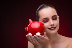 The young woman with red piggybank Stock Photography