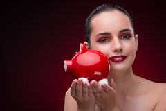 The young woman with red piggybank Stock Photo
