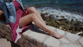 Young woman in red polka-dot dress sitting barefoot on stone fence. Close-up view focused on skinny tanned female legs