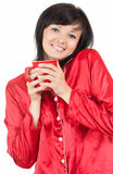 Young woman in red pyjamas drinking morning coffee Stock Photos