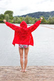 Young woman in red raincoat and bikini Royalty Free Stock Image