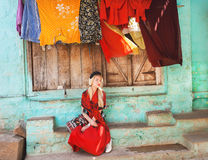 Young woman in red relaxing on the porch of traditional indian rural house with colorful clothes dries after washing. Stock Photography
