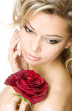 Young woman with a red rose. Close-up portrait of a young blond holding a rose Stock Photo