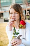 Young woman with red rose and chocolate Royalty Free Stock Images