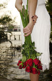 Young woman with red roses near the river. Red roses in woman hand before sunset Stock Images