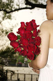 Young woman with red roses near the river. Red roses in woman hand before sunset Stock Photography