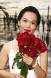 Young woman with red roses near the river. Red roses in woman hand before sunset Royalty Free Stock Photography