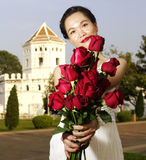 Young woman with red roses in the park. Red roses in woman hand near old fortification Stock Photos