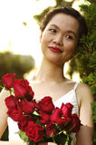 Young woman with red roses in the park. Red roses in woman hand before sunset Royalty Free Stock Photography