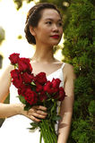 Young woman with red roses in the park. Red roses in woman hand before sunset Royalty Free Stock Image