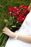 Young woman with red roses in the park. Red roses in woman hand Stock Photography