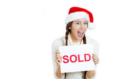 Young woman in red santa claus hat holding a sold sign with hands Stock Photo