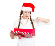 Young woman in red santa claus hat opening gift, very upset at what she received Stock Image