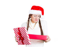 Young woman in red santa claus hat opening gift, very upset at what she received Stock Photography