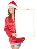 Young woman in red Santa hat with blank poster Royalty Free Stock Photos