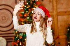 A young woman in a red Santa hat makes selfi for Christmas royalty free stock photos
