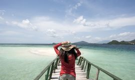 Young Woman with red shirt holding hat at beach for holiday. With beautiful blue skies Stock Photography