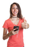 Young woman in a red shirt likes music Stock Photo