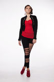 Young woman in red shirt, modern jacket, leggings with holes, re Royalty Free Stock Photography