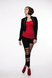 Young woman in red shirt, modern jacket, leggings with holes, re Royalty Free Stock Photo