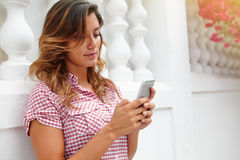 Young woman in red shirt texting on smart phone Royalty Free Stock Photos