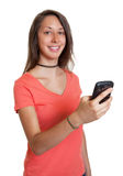 Young woman in a red shirt writing a message Stock Photography