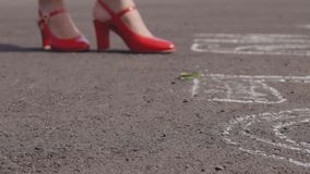 Young woman in red shoes stands on asphalt and drops scarlet rose. stock video footage