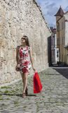 Woman with Red Shopping Bag in a City. Young woman with a red shopping bag walking on a small street in an old city Stock Photography