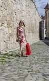 Woman with Red Shopping Bag in a City. Young woman with a red shopping bag walking on a small street in an old city Royalty Free Stock Images