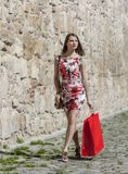 Woman with Red Shopping Bag in a City. Young woman with a red shopping bag walking on a small street in an old city Stock Photos