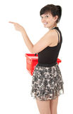Young woman with red shopping basket showing somet Stock Photo