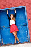 Young Woman in Red Skirt, Blue Door Royalty Free Stock Photos