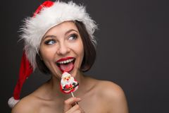 Young woman in a red skirt and santa claus hat on a light backgr Stock Images