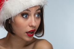 Young woman in a red skirt and santa claus hat on a light backgr Stock Photos