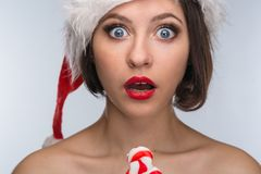 Young woman in a red skirt and santa claus hat on a light backgr Stock Photography