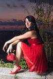 Young woman in red sleeveless dress against sunset sky. Portrait of young woman in red sleeveless dress. Attractive long haired brunette in red sundress posing Royalty Free Stock Image
