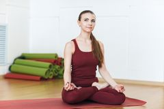 Young Woman in a red suit Doing Yoga Exercises In Gym, Sport Fitness Girl Sitting Lotus Pose Meditation Relaxation. stock image