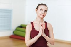 Young Woman in a red suit practicing meditation on the gym in yoga class. Relaxation and Stretching. Woman holds her hands in Nama. Ste posture, do yoga lotus Royalty Free Stock Photography