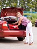 Young woman with a red suitcase in the car Stock Image