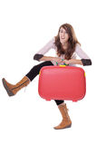 Young woman with red suitcase making funny faces Royalty Free Stock Image