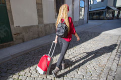 Young woman with red suitcase is on the pavement. Royalty Free Stock Photos