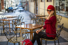 Young woman with red suitcase talking on the phone sitting at a table. Royalty Free Stock Photo