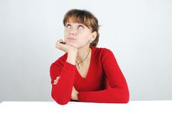 Young woman in a red sweater. A pensive young woman in a red sweater at the desk, isolated on white stock images