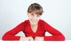 Young woman in a red sweater. A happy young woman in a red sweater at the desk, isolated on white stock photos